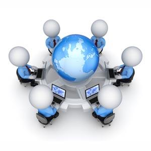 Programozók körbeülnek egy asztalt, laptopokkal, középen földgömb